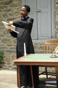 Juneteenth: Youth re-enactor portrays William Still, free-born Black, abolitionist, clerk for the Pennsylvania Society for the Abolition of Slavery, reads at Anti-Slavery meeting in Philadelphia.