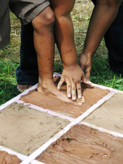 """Summer campers mold their feet in cement, for use in a """"future"""" public sculpture which will help today's children understand the secrets of freedom seekers who journeyed to achieve freedom along the Underground Railroad."""